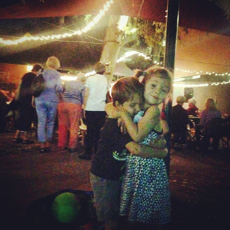Chase and a school friend hug under the twinkle lights on the Duck & Decanter patio.  Laughter, music and food contribute to the atmosphere.